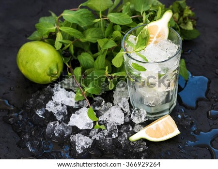 Mojito cooking set. Bunch of fresh mint, lime, chipped ice and cocktail glass over black slate stone backdrop, selective focus - stock photo
