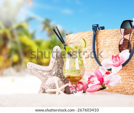 Mojito drink, sunglasses and flip-flops with tropical beach background, summer accessories - stock photo