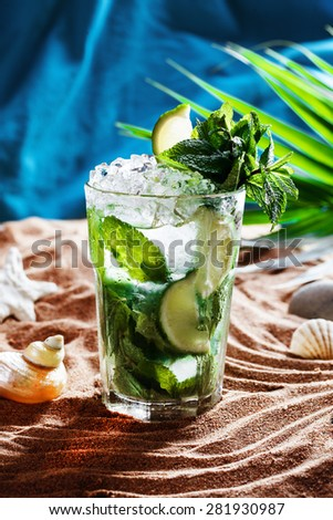 Mojito with lime and mint in a still life on the sand by the sea ocean water, tea, water