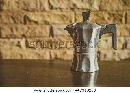 Moka pot ,Italian coffee maker  on wooden table and sandstone background,vintage style.