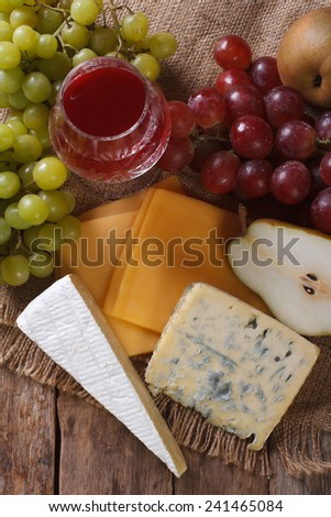 Molded cheese, wine and fruit on the table close-up. Vertical view from above