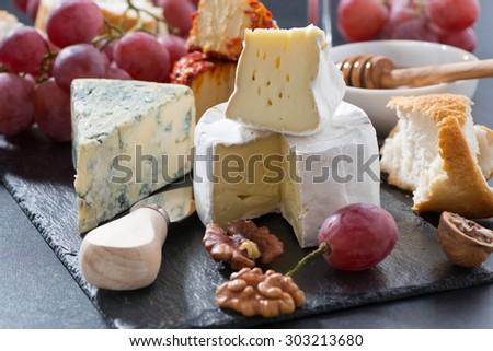 molded cheeses and snacks on the blackboard, horizontal - stock photo