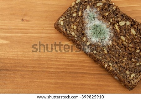 Moldy bread in wooden table. Unhealthy food. Spoiled food. - stock photo