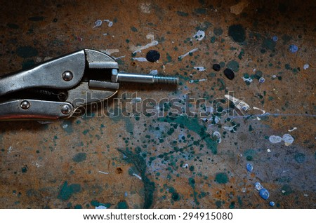 Molegrips holding a bolt tight on a grungy messy background