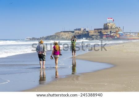 MOLLENDO, PERU, MAY 20, 2014: Tourist family walks on beach - stock photo