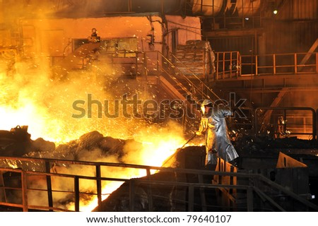 Molten hot steel pouring and worker - stock photo