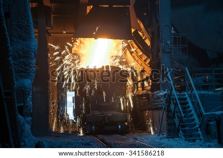 molten metal pouring into ladle  - stock photo