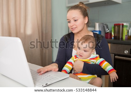 mom and baby. a young mother working with laptop in kitchen