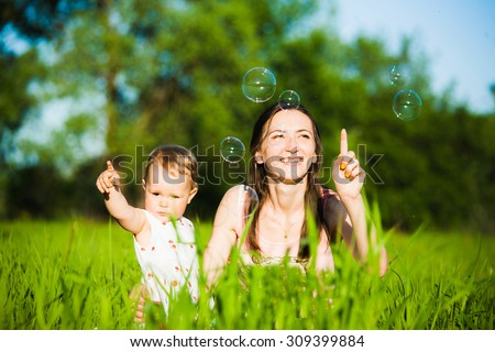 Mom and baby girl laying on grass and cheerfully catching soap bubbles with fingers. Happy family concept. - stock photo