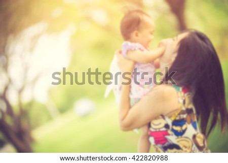 Mom and baby little girl on the blurry background vintage color - stock photo