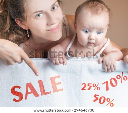 Mom and baby lying on white blanket. Advertising banner sign - Mom is pointing down on text with word discount and percent. Child stares down at inscription. Mother smiling and looking at camera - stock photo