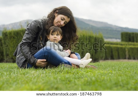 Mom and baby playing outdoors at park - stock photo