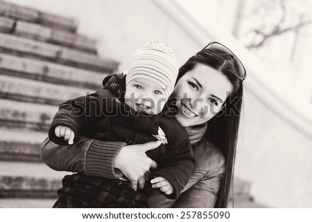 mom and baby son having fun outdoors - stock photo