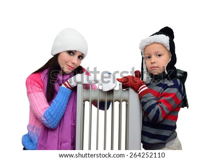 Mom and boy in mittens and hats bask near radiator - stock photo