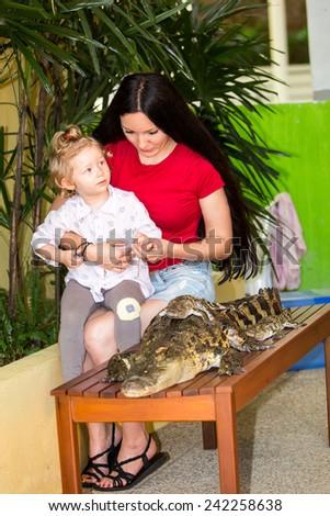 Mom and child girl on Crocodile farm in Phuket, Thailand - stock photo