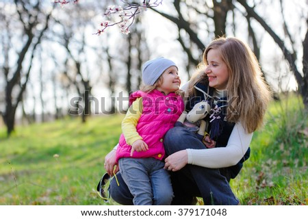 Mom and cute little girl in a blossoming spring garden