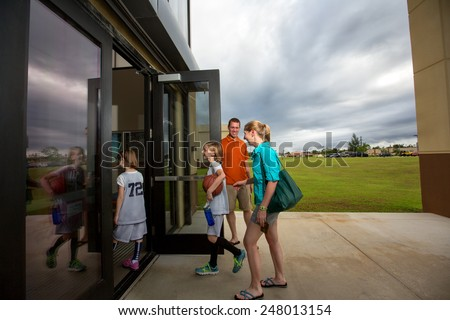 Mom and dad at the gym door taking the kids to their basketball game - stock photo