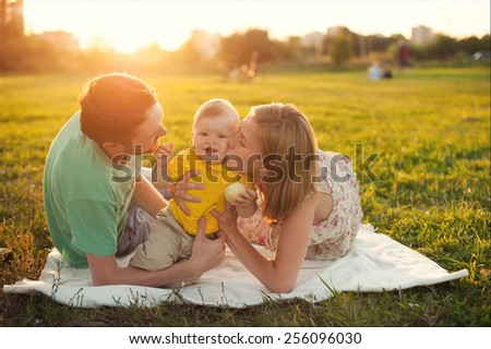 Mom and dad kiss on the cheek baby - stock photo