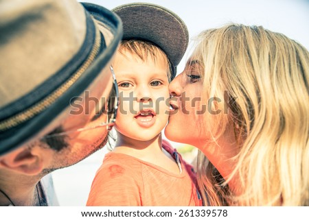 Mom and dad kissing their handsome son - Family and baby outdoors - stock photo