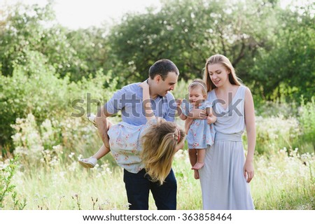 Mom and dad playing on the nature and hugging two daughters, family, childhood, family values, life style
