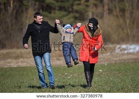 mom and dad raise child up outdoors - stock photo