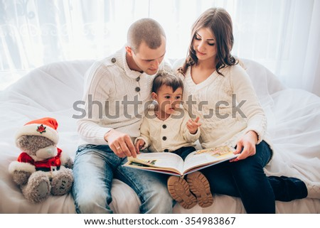 Mom and dad read a book to his baby son