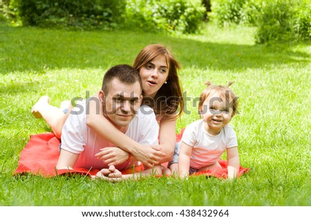Mom and Dad spend time with their little daughter in the park