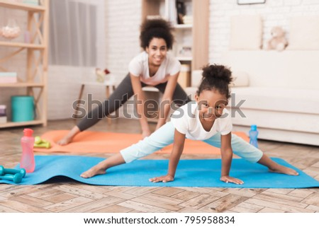 Mom and daughter are doing yoga at home. They are sitting on a rug, next to them are dumbbells. A girl and a woman are mulattoes.