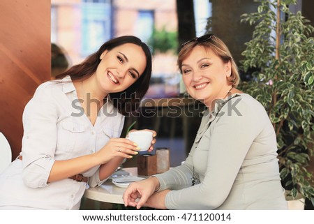 Mom and daughter are in the cafe. They are laughing and looking into the camera. Daughter is holding a cup in her hands