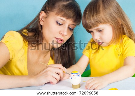 Mom and daughter are preparing for the Easter painted eggs - stock photo