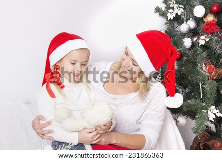 Mom and daughter at Christmas sitting near the fireplace in an embrace and smile