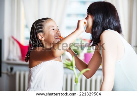 Mom and daughter brushing teeth - stock photo