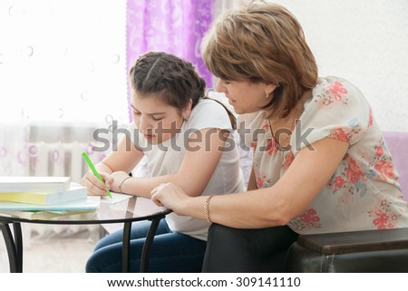 Mom and daughter doing homework at home.