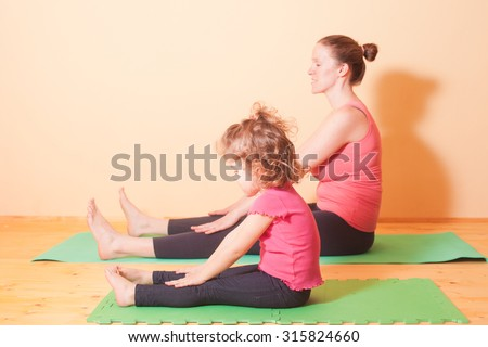 Mom and daughter doing yoga exercises on green rug - stock photo