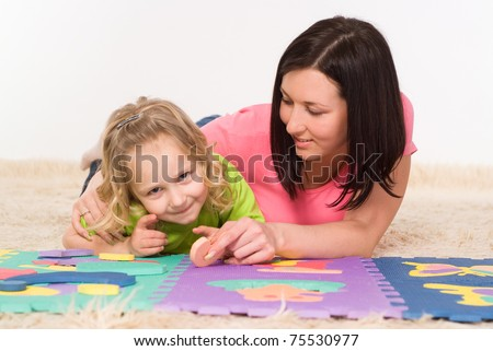 mom and daughter drawing on the carpet on white