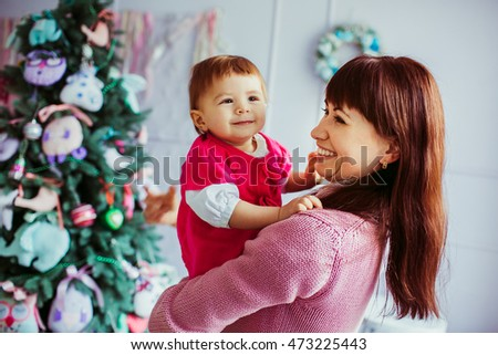 Mom and daughter dressed in pink tones stand before Christmas tree