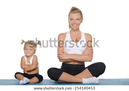 Mom and daughter engage in fitness on blue mat