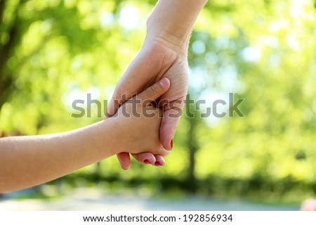 Mom and daughter hands, outdoors - stock photo