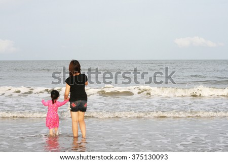 Mom and daughter have fun on the beach