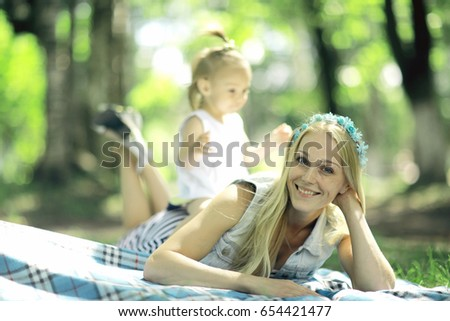 Mom and daughter having fun and playing in the summer park