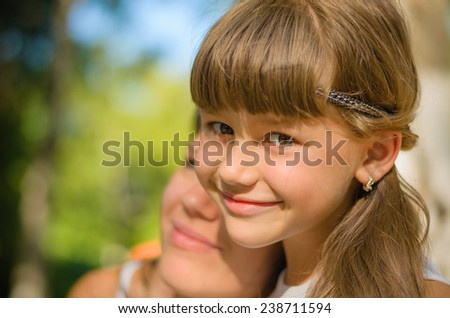 Mom and daughter hugging each other, smiling, radiate happiness and joy - stock photo