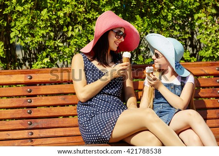Mom and daughter in hats and sunglasses eating ice cream in a park sitting on a bench. mother and child - stock photo