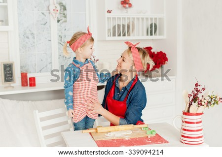 Mom and daughter in the kitchen - stock photo