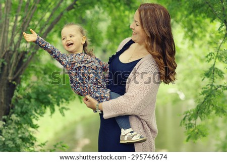 Mom and daughter in the park a young family - stock photo