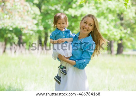 Mom and daughter in the same dress in the forest