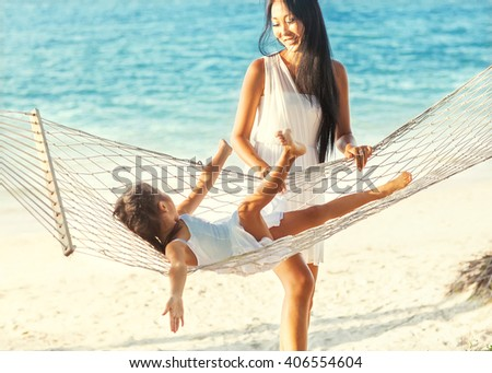 Mom and daughter lying in a hammock by the sea enjoying nature and tropical palm trees, happy. Mothers day. - stock photo