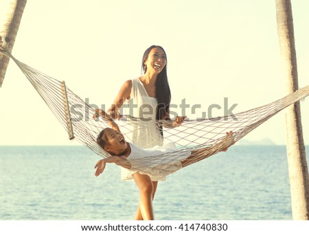 Mom and daughter lying in a hammock by the sea enjoying nature and tropical palm trees, happy. Mothers day.