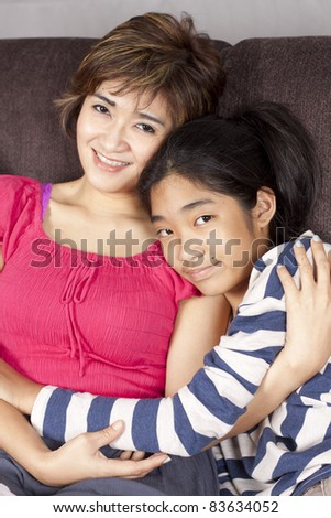 mom and daughter, mother in pink dress hug her daughter happy. - stock photo