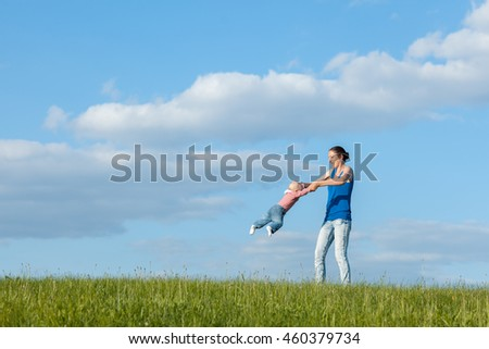 Mom and daughter on a meadow against the sky. Mom turns daughter