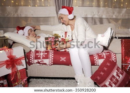 Mom and daughter on the sofa among a large number of gifts. Festive time of joy and love. Family time.